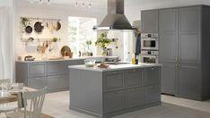 Ett ljust, luftigt kök med BODBYN kökslucka i grått och en köksö.