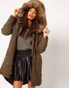 a funnel neckline, a drawstring hood with an oversized faux fur collar, dropped shoulder seams with button down tabs, zip fastening with a press stud placket through the front, a drawstring yoke and waist, slant pockets to the hips, deep flap pockets and a dipped fishtail hem with a split detail and drawstring design