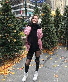 Maggie Lindemann. Ripped black jeans with fishnet tights underneath. Cold weather outfit. White fluffy ear muffs. Poofy pink jacket.
