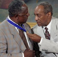 Comedian Bill Cosby, right, admires baseball legend Hank Aaron's Presidential Medal of Freedom