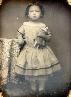 This is my newest acquisition out of Spain. 1/6th plate daguerreotype of a sweet little girl in her off shoulder dress holding her china head doll. The dress is actually tinted peach and the dolls dress is tinted lilac. Image came in a full case and has old paper seals.