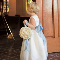 Carrying a pomander of lush white blooms, the flower girl walked down the aisle in an ivory dress with a light blue sash tied around her waist.