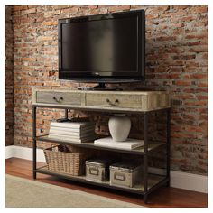 Bring rustic industrial style to your space with the Bay View TV Stand. This pieces features a metal frame supporting the wood shelving. Details like rivets and bracing further the industrial feel. Two drawers offer a convenient place to stash necessities close at hand. The mix of brown metal and sea oak finish wood are neutral enough to complement any decor styling.