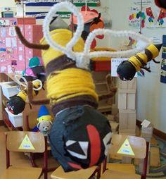 * De kinderen bedekken de wc-rol met wol. Kop is gemaakt van een stuk krantenpapier gewikkeld in zwart crêpepapier.