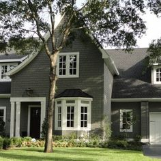 Traditional Home Exterior Design among Grey Wall Siding Combined with White Painting for Garage Doors also