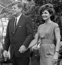 Dedicated: JFK and his wife Jackie hold hands as they meet with delegates in 1962. Previously unreleased interviews have revealed she begged her husband not to send her to safety during the Cuban Missile Crisis that year.