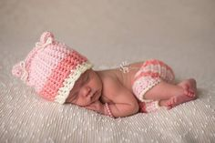 This kitten hat and shorties set in coral, cream and pink is a delightfully unique prop outfit for newborn girls. It features a beautiful knit-like post stitch and adorable tiny ears tied with a bow.