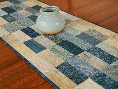 This quilted batik table runner features shades of blue ranging from aqua to dark navy, along with creamy whites with hints of gold, tan, and taupe. The size is approximately 16 X 45 (41 X 114 cm) - a versatile size for use on a dining table, coffee table, or bedroom dresser. I