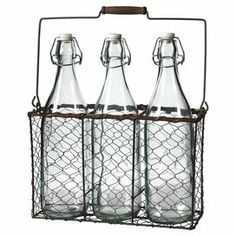 """Featuring 3 milk bottles and an accompanying basket, this vintage-inspired design lends a charming touch to your kitchen or breakfast nook.  Product: 3 Bottles and caddyConstruction Material: Metal and glassColor: Black and brownDimensions: 12.2"""" H x 10.6"""" W x 4.7"""" D (overall)Cleaning and Care: Wipe with a dry cloth"""
