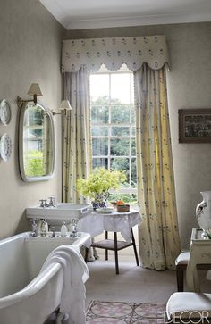 The curtains in a guest bath are of a Colefax and Fowler fabric, the needlepoint rug is English, and the tub is original to the house.   - ELLEDecor.com