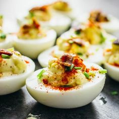 Each deviled egg includes a generous squeeze of sriracha and is topped with crispy crumbled bacon, fresh chives, and ground paprika.
