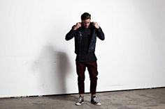 Shop this look for $73:  http://lookastic.com/men/looks/burgundy-chinos-and-black-high-top-sneakers-and-navy-crew-neck-sweater-and-black-denim-jacket/777  — Burgundy Chinos  — Black High Top Sneakers  — Navy Crew-neck Sweater  — Black Denim Jacket