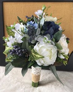 A one of a kind addition to make your special day one to remember. This beautiful silk bouquet not only looks fresh and realistic but will be a keepsake for a lifetime without the worries of wilting fresh flowers. This gorgeous bouquet was handmade in shades of ivory, white, navy blue