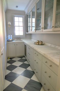 Amazing galley butler's pantry with white & black checkered floors, ivory glass-front gray kitchen cabinets with marble countertops, gray walls paint color and Bryant Sconce.