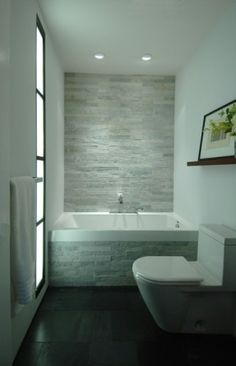 Modern bathroom. Love the stacked stone tub surround and backwall.  Great darkwood floors