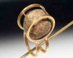 A cage of 14K gold loosely holds a perfect wave-polished granite.  The stone is loose in the cage and makes a pleasing rattle.  It can also be worn as a pendant by sliding a chain through the shank.