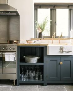Love the moody grey tones mixed with the warm brass and copper highlights in this charming Shaker kitchen #deVOLKitchens