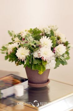 Take a bit of summer indoors with this dainty mix of summer favorites – dahlias and hydrangeas – in a yummy white and pink color combo with lush green snow mountain and geranium leaves as fillers.