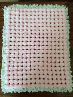Pink and white pom pom blanket