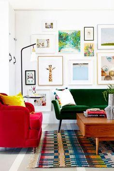 decoração com sofá colorido, sofá verde e poltrona vermelha, vários quadros na parede