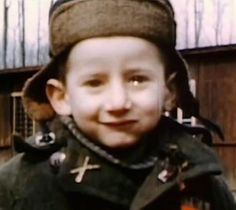1945 - Little boy in liberated Nazi concentration camp smiles in the camera and starts to cry. BBC WW2 in color