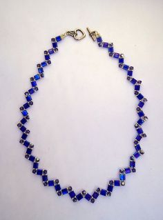 Tila bead necklacechoker style necklacezig zag by JoolsbyAverilBeaded necklace in zig zag pattern with rainbow capri blue tila beads,tanzanite swarovski crystals and silver Miyuki seed beads antique silver heart toggle. 17 inches in length. Swarovski Crystal Necklace, Crystal Bracelets, Beaded Necklace, Swarovski Crystals, Bead Jewellery, Jewelry Necklaces, Blue Choker, Beaded Jewelry Patterns, Diy Necklace Patterns