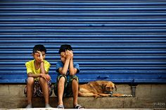 Two nepalese boy with a dog sitting near the metal shutters on the street in kathmandu nepal Dog Photography, Street Photography, Metal Shutters, Nepal Kathmandu, West Bengal, Mustang, Thailand, India, Culture