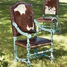 """Rustic - CRACKLED TURQUOISE ARM CHAIR  #215129         These hair on hide chairs feature a crackled turquoise finish on a European Beechwood frame. Brown and white cowhide covers the inback and outback with a comfortable leather foam filled seat. Accented with large and small nailhead trim. 24""""w x 28 1/2""""d x 47""""h USA. $1,398.00"""