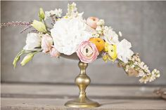 Gold container with classic centerpiece in a crescent style.