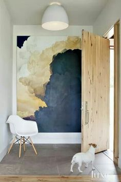 Modern entry with light wood door and incredible abstract art in some bold color choices