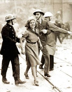 A female worker in the City still smiling after being rescued from a London building wrecked by a bomb dropped in a daylight Luftwaffe raid - 1940