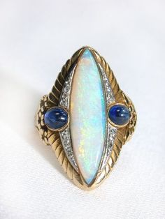 Excellant Example of Art Deco Egyptian Revival, Marquis Cut Opal, Cabochon Sapphires, White & Yellow Gold and Diamonds Ring, ca. 1920.