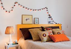 Para não ter de investir em marcenaria planejada no quarto, destaque outros detalhes da decoração. Aqui, o truque foi turbinar a cama com almofadas coloridas. O pisca-pisca acima da cabeceira também chama atenção