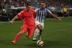 Lionel Messi of F.C. Barcelona (L), duels for the ball with Sergi Darder of Malaga CF during the La Liga match between Malaga CF and FC Barcelona at La Rosaleda studium on September 24, 2014 in Malaga, Spain.