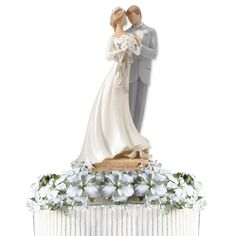 """Kim Lawrence remind brides and grooms that the """"Two shall become One"""" with the elegantly designed Legacy of Love Wedding Cake Topper Figurine. Featuring a clear acrylic oval base with hand painted silver and gold metallic accents and 13 inlaid crystals, this piece allows you to choose to dress the groom in a black suit and bow tie for an additional fee. You can%2..."""