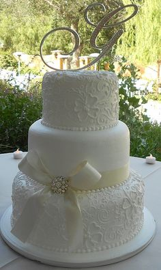 White elegant wedding cake - probably wouldn't put a big bow on the cake though!