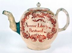 """There are four known English creamware teapots inscribed """"No Stamp Act"""" and """"America, Liberty/Restored."""" One from the William Guthman collection, with dark lettering, sold to the Smithsonian for $99,450 at Northeast Auction in October 2006. This one, with red lettering, went to C.L. Prickett Antiques for $130,000. Both pots had repairs. Two other examples are in the collections of Colonial Williamsburg and the Peabody Essex Museum."""