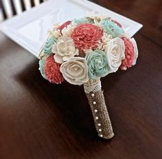 ivory, coral, and mini and features shell, mum, rose, and gardenia sola flowers and is embellished with pearls and natural babies breath. The stem is wrapped with burlap with an antique lace collar and pearls.