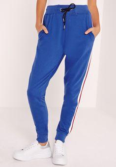 Cette saison, il va y avoir du sport. Adoptez vite ce jogging bleu roi avec rayures rouges et blanches pour un look aussi cool que confortable, et en plus la veste assortie est disponible. Portez les deux ensemble avec des baskets, à la co...