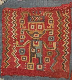 Huari textile fragment; cotton warps and camelid wefts; tapestry; frontal figure with arms held out to sides, wearing a patterned tunic, ear spool...