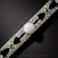 Art Deco Opal, Demantoid Garnet and Diamond Bracelet. Something delightfully different in an original Art Deco bracelet - circa 1925. The rather rare and distinctive combination of opals and demantoid garnets are most often seen in jewels from the turn-of-the-twentieth century Art Nouveau period. Here they have been effectively incorporated to soften and feminize the typically bold and striking effect of Art Deco...