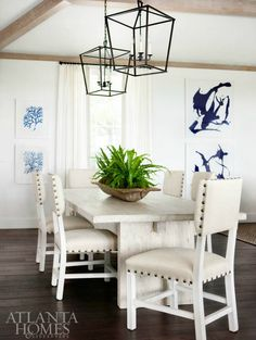 coastal beach style dining room with white marble table, light cream chairs, wrought iron lantern pendant lights, blue and white artwork, light wooden beams