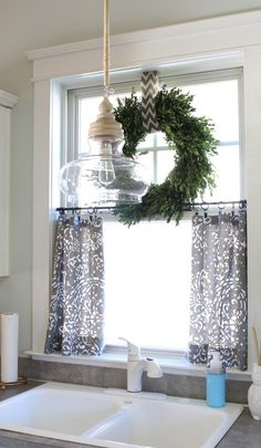 Boxwood wreath on top of small curtains for kitchen window. Have to look into this for mine maybe? Don't know if I can handle not having blinds so I don't have to see in my neighbors houses all winter though...