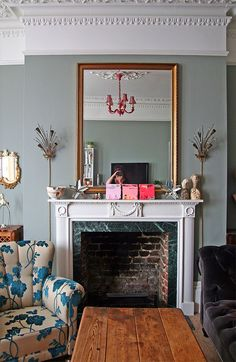 Gilt framed mirror above fireplace in French apartment living room ...