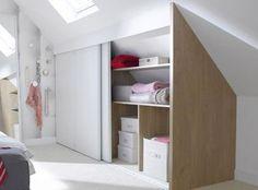 Un dressing sous pente en bois et blanc, à portes coulissantes, monté sur les parties basse des combles d'un studio, bien insérée et apporte une touche de déco à la chambre.