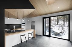In the kitchen, the architects reigned in the house's high ceilings for a more intimate feel; its lower height also tastefully hides unsightly ducting necessary for ventilation. Beneath the bar sit two Kaysa Black Bar Stools by Baxton Studio. A Gessi faucet complements a Blanco Modex sink.