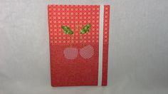 Caderno encapado em tecido com aplicação de cerejas.