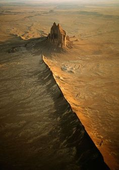 """Shiprock is a monadnock rising nearly 1,583 feet (482.5 m) above the high-desert plain on the Navajo Nation in San Juan County, New Mexico, USA. It has a peak elevation of 7,177 feet (2,187.5 m) above sea level. It lies about 10.75 miles (17.30 km) southwest of the town of Shiprock, which is named for the peak. Shiprock is composed of fractured volcanic breccia and black dikes of igneous rock called """"minette""""."""