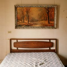 Motel room with unmade bed and landscape painting. Photo by Aaron Ruell.