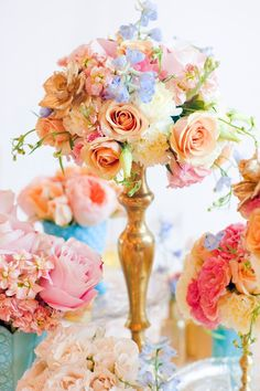 Blue Pink Peach and Cream Flowers in Gold Candlestick Vase